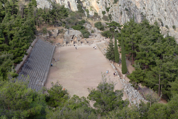 An aerial photo showing the Ancient Stadium of Delphi among the dense vegetation of the area and the nearby cliff.
