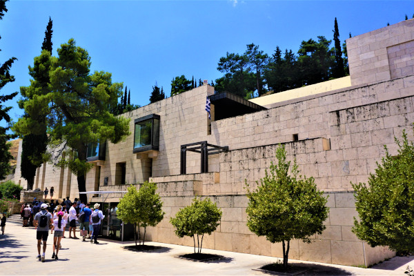 The front side of the Delphi Archaeological Museum with some guests approaching the main entrance.