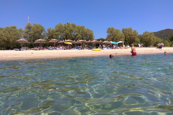 A picture taken from the sea depicts people in the water and umbrellas and sunbeds at the Develiki Beach.
