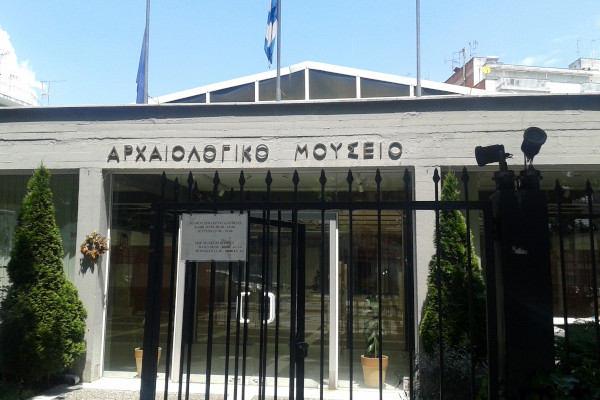The main entrance of the Archaeological Museum of Drama behind a metal fence.