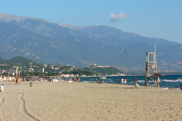 The long beach of Nei (Neoi) Pori with a lifeguard tower close to the sea and the Mount Olympos in the background.