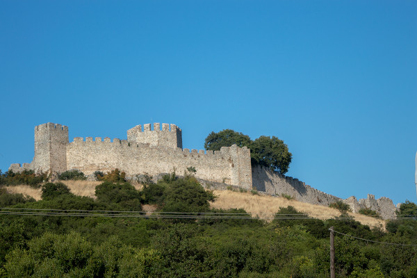 The walls of the castle of Platamonas among the dense vegetation and the blue sky in the background.