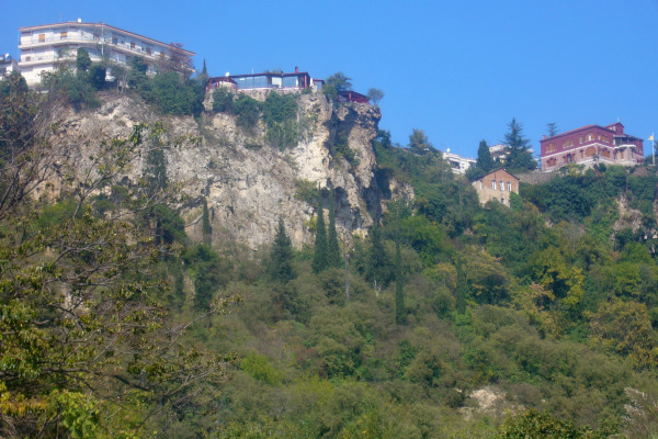 A steep rock and the cafeteria «High Rock» on top of it among the dense vegetation of the area.