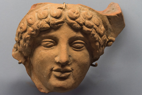 An exhibit of the Archaeological Museum of Eretria depicting a clay-head of a woman dating from ca.500 BCE.