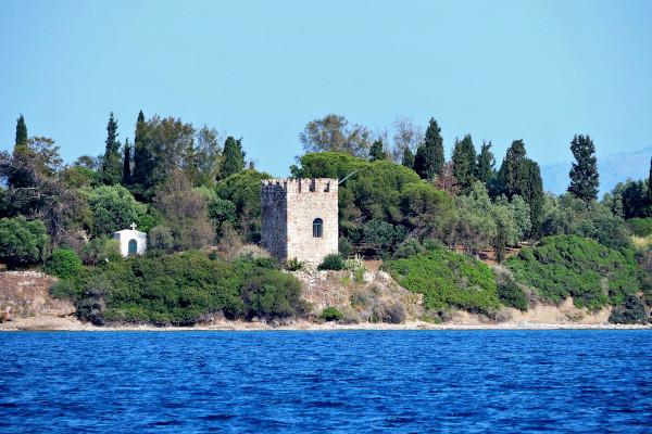 A photo of the Venetian Tower on the coast of Agia Triada Island in dense vegetation.