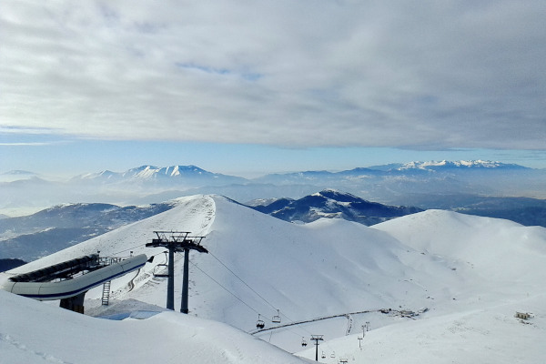 A panoramic picture of the snowy slopes and the facilities of the Falakro ski resort.