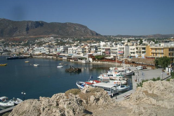 An overview of the Hersonissos Port that includes some boats anchored by the coast and a part of the settlement.
