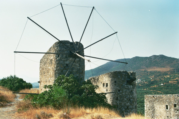 A photo showing the Windmills of Selí Ambélou with the surrounding mountains in the background.