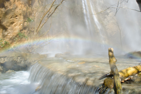 The small water droplets and the mist created bu the waterfall form a small rainbow.