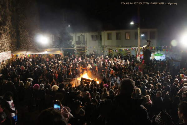 Crowd and dancing people around a fire during the Carnival custom of Tzamales in Ioannina.