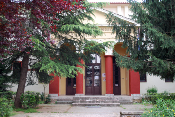 The main entrance of the Zosimaia Library in Ioannina among the green trees of the front yard.