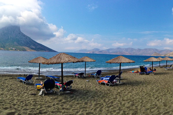 A picture of the Masouri beach on Kalymnos with the sea and the island of Telendos in the background.
