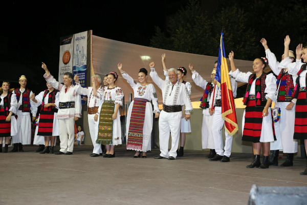 Members of a Romanian cultural association wearing traditional clothes are greeting the audience from the stage.