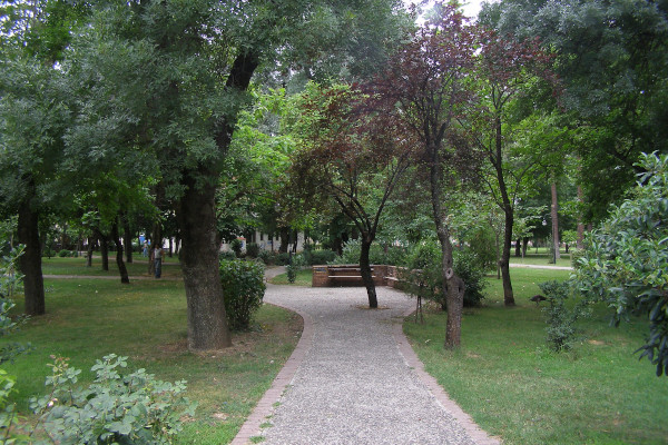 One of the paths in Pafsilipo Park in Karditsa among the trees and the green landscape.