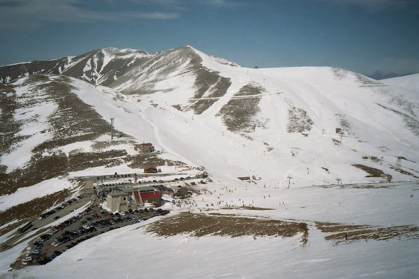 A photo of the Velouchi Ski Center including the slopes, the infrastructure, and the parking place.