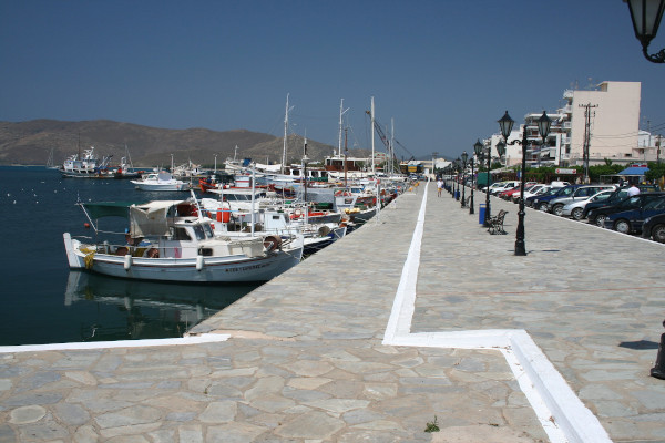 The seafront promenade of Karystos with many fishing and sailing boats anchored by the coast.