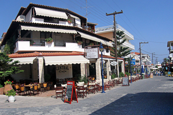 A central street of Hanioti with restaurants, cafeterias, and outdoor seats on the pavement.