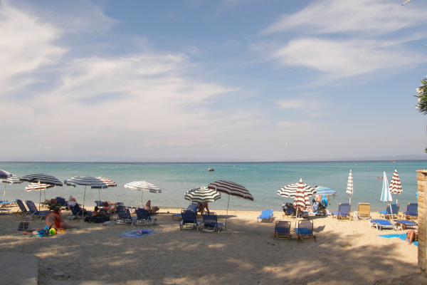 People with umbrellas and sunbeds at the Hanioti Beach in Halkidiki.