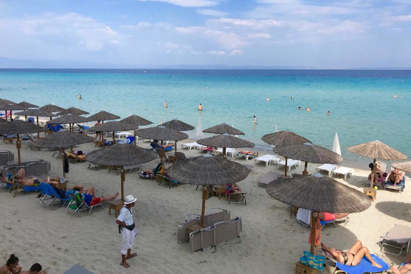 Numerous umbrellas and sunbeds lying on the Kallithea Beach of Halkidiki.