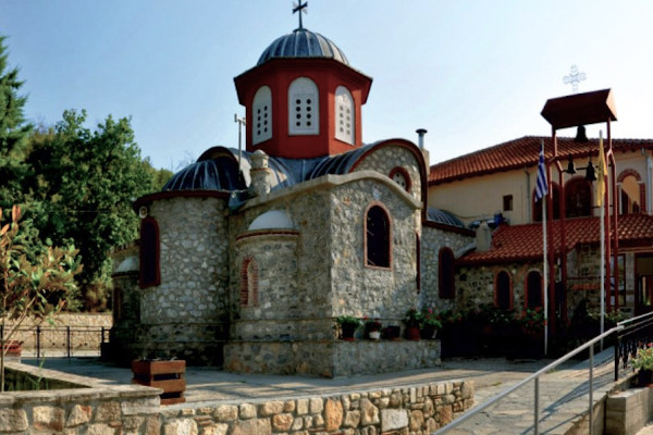 A stone-built church with a red dome that has white windows in the yard of the monastery.