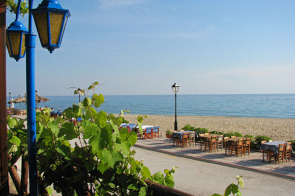 Numerous restaurant tables at the seafront promenade and a part of Nea Skioni Beach of Halkidiki.