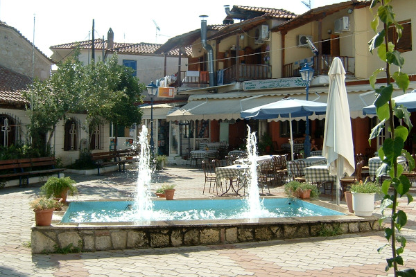 A fountain in a square of Pefkohori surrounded by restaurants and tavernas.
