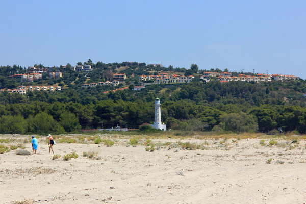 The lighthouse of Possidi and the green hill with many second homes in the background.