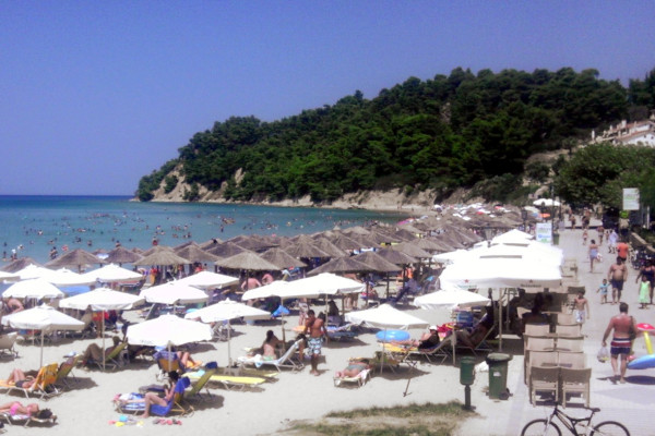 An image showing numerous people, umbrellas, and sunbeds at a part of Siviri Beach of Halkidiki.