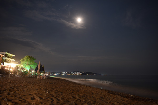 A night capture showing the beach of Skala Fourkas in Halkidiki under the moonlight.
