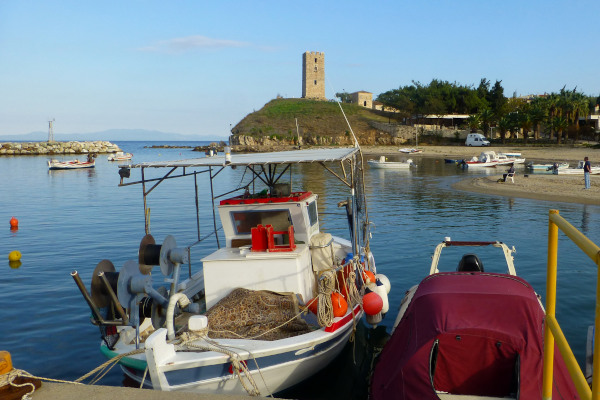 The port of Nea Fokea with small fishing boats and the hill with the Byzantine Tower of St. Paul in the background.