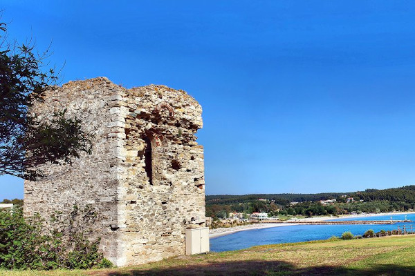 The remains of the Stavronikita Tower with the sandy beach and the blue sky in the background.