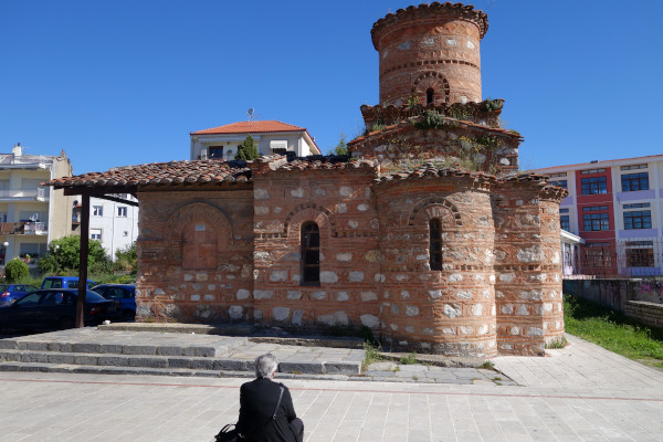 A picture of the Byzantine Church of Panagia Koumpelidiki in Kastoria with an old woman looking at it.
