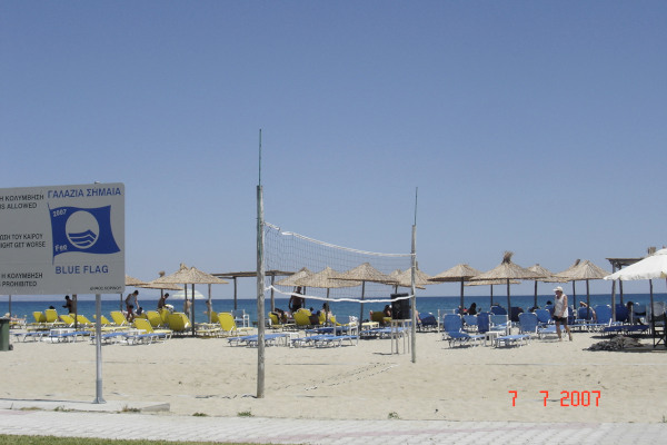 A beach volley court, a blue flag sign, and numerous umbrellas and sunbeds at the Korinos beach of Katerini.