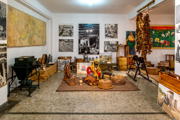 The interior of one of the exhibition rooms of the Kavala Tobacco Museum with many artifacts and pictures on the walls.
