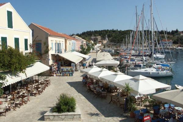 Shops and restaurants on the coastal promenade of Fiskardo and many sailing boats anchored at the port.