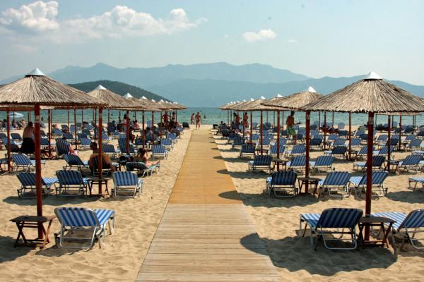 Numerous sunbeds and umbrellas at the beach bar of the Keramoti (Ammoglossa) Beach.