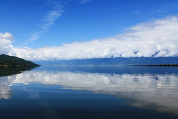 The waters of the Kerkini Lake reflecting the clouds and the blue sky.