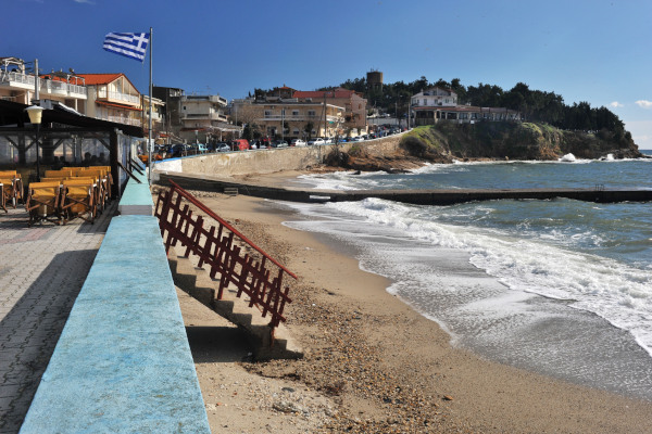 A photo showing the beach of Fanari Port of Rhodope by the tavernas and the buildings of the Fanari settlement.