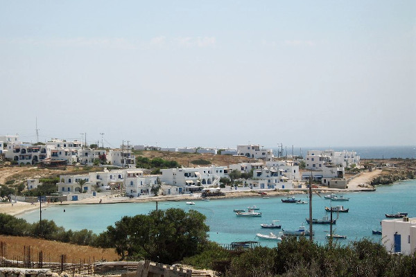 An overview of the Chora of Ano Koufonissi and the small bay with numerous boats in front of it.