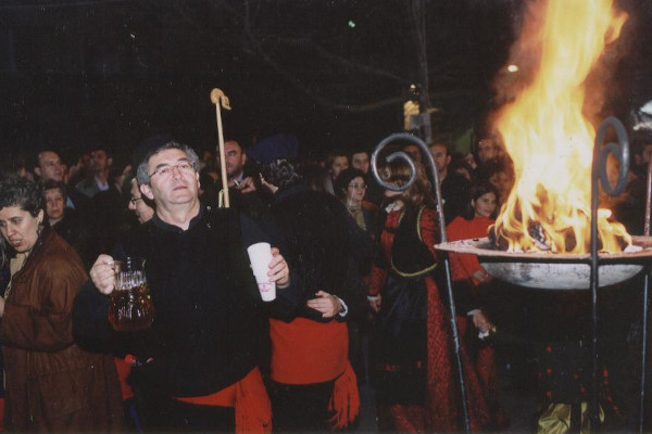People in traditional clothes, holding a jug of wine, are singing around the lit metal cresset.