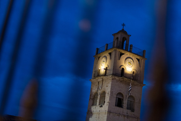 The illuminated top of the clock tower of Kozani during the dusk.