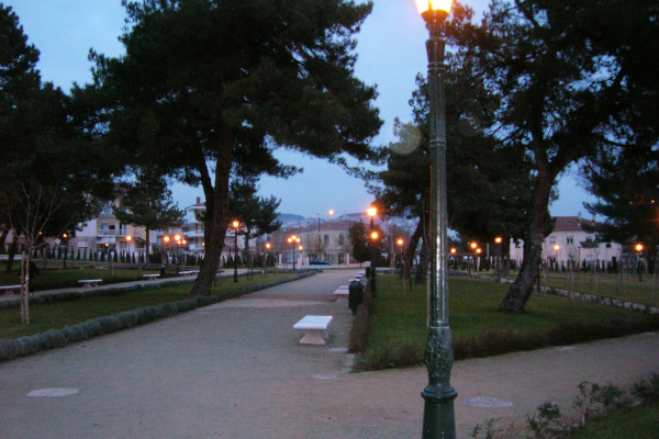 The paths of the Municipal Park of Kozani among the trees during the evening.