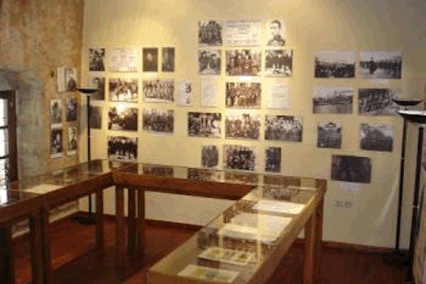 A room of the Museum of Contemporary Local History of Kozani, with exhibits in displays and photos hanging on the walls.