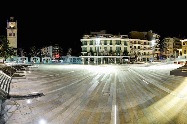The illuminated Nikis Square of Kozani during the night, with the clock tower visible on the left of the picture.