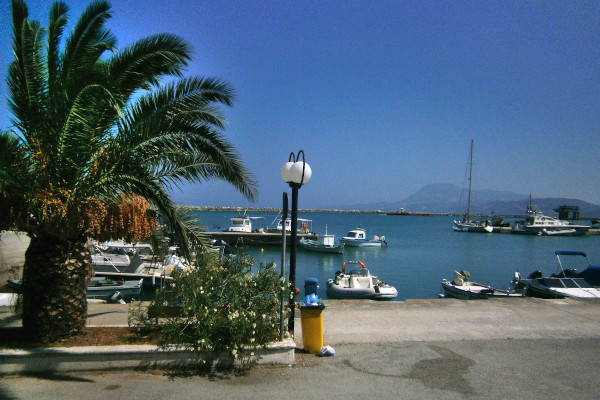 A picture depicting a part of the promenade of Paralia Kymis and numerous small boats anchored in the port.