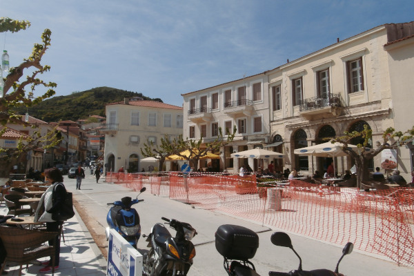 Some tables at the central square of Kymi and the surrounding buildings that host cafeterias and restaurants.