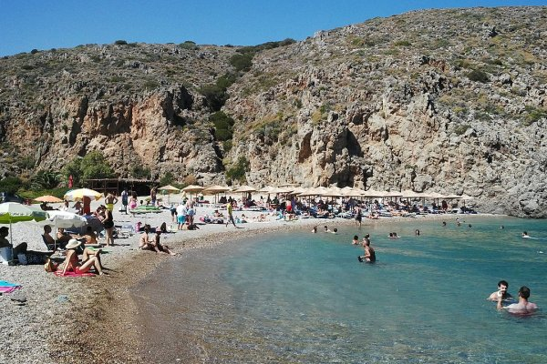 A photo showing people sun beds and umbrellas at the Chalkos Beach of Kythira island.