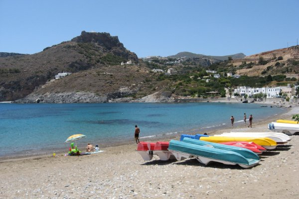 Water pedalboats lying on the beach and some people enjoy the weather on Kapsali Beach on Kythira island.