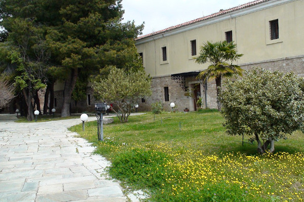 The the main entrance of the Archaeological Museum of Lamia among trees and green vegetation.
