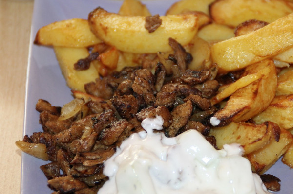 A close up photo of a dish that includes tzatziki, gyros meat and french fries.